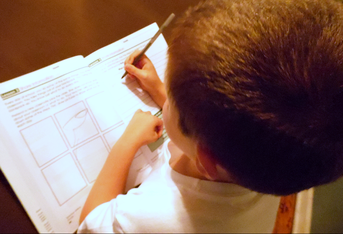 Benjamin practicing writing in his Spectrum workbook - 1st grade